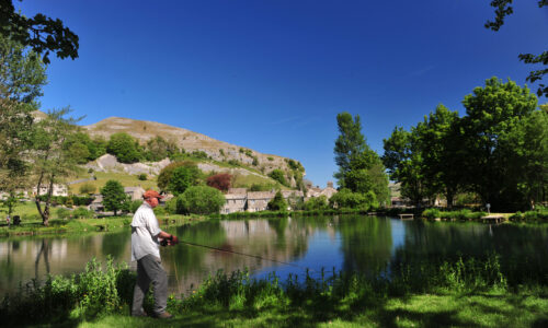 2nd June 2020 The Kilnsey Park fishery , near Skipton, open after Coronavirus lockdown. Pictured new fisheries manager Leigh Fidell fishing on the lower lake with the back drop of Kilnsey Crag. Picture Gerard Binks